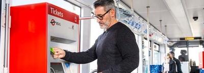 Ein Mann steht am Ticketautomaten