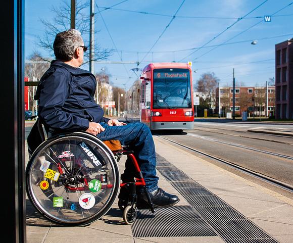 Rollstuhlfahrer wartet auf Straßenbahn