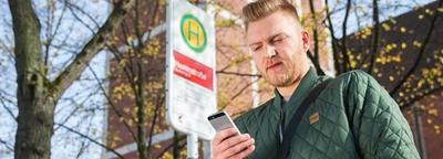 junger Mann schaut auf sein Telefon
