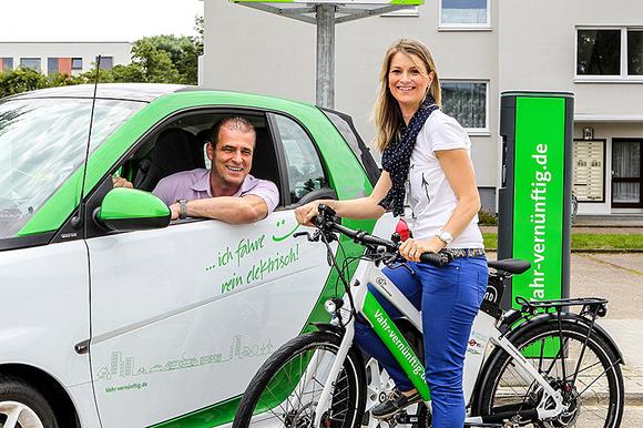 Mann mit E-Auto und Frau mit E-Bike
